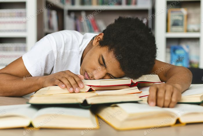 Tired guy napping on books stack in library