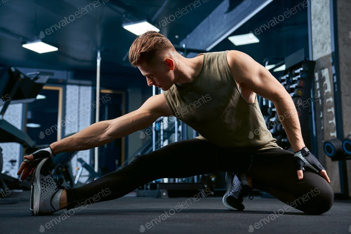 Bodybuilder stretching upper body in gym