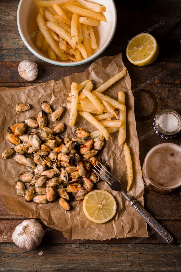 Mussels with lemons and French fries on the metal background vertical