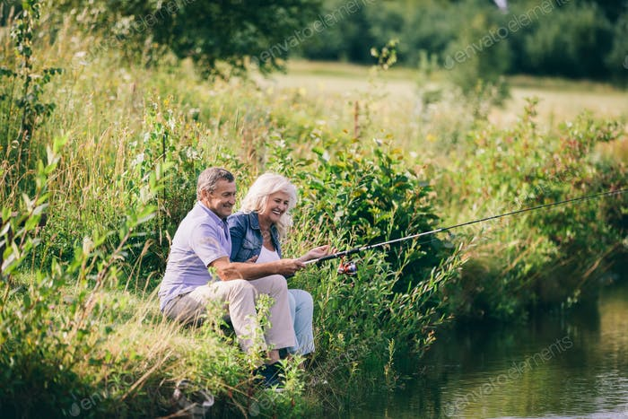 Senior couple fishing by the water.