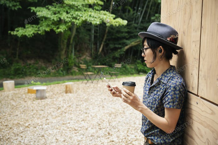 Japanese woman wearing glasses and hat standing outside Eco Cafe, holding paper cup.