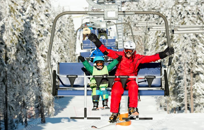 Ski instructor with little boy enjoying on ski lift