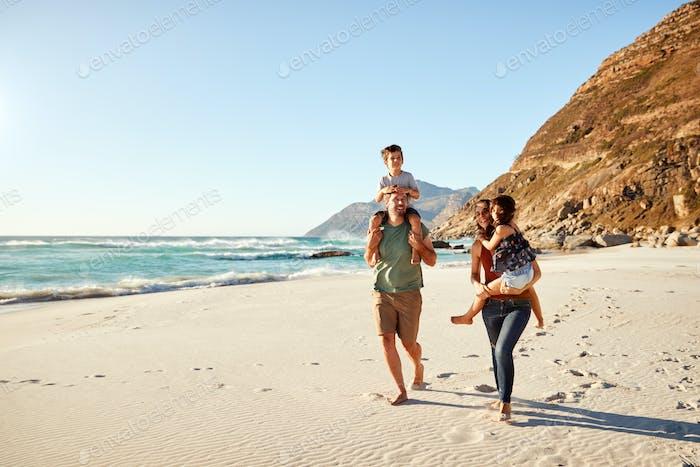 Pareja blanca de adultos medio caminando a lo largo de una Playa en unas vacaciones familiares llevando a sus Niños, Duración completa
