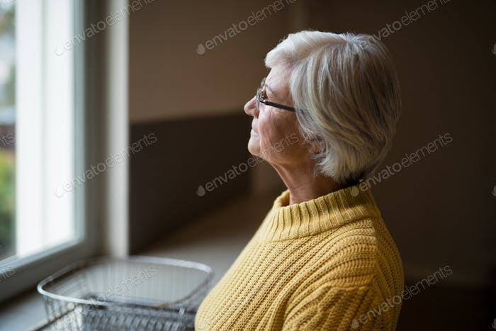 Thoughtful senior woman looking through kitchen window