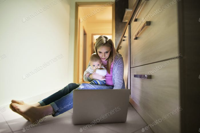 Schöne Mutter mit Sohn in den Armen, arbeitet am Laptop.