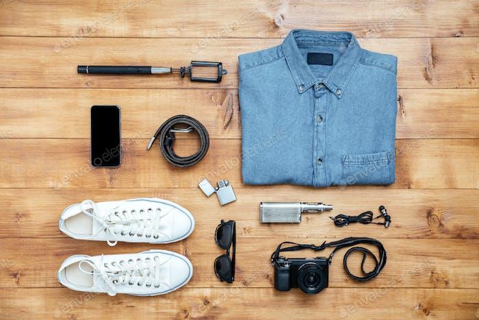 Travel concept shoes, shirt, mobile phone, eyeglasses, belt, lighter, camera