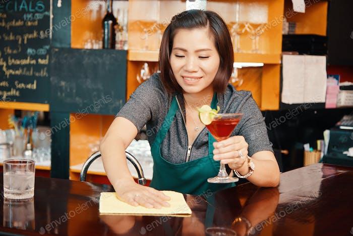 Barwoman wiping bar counter