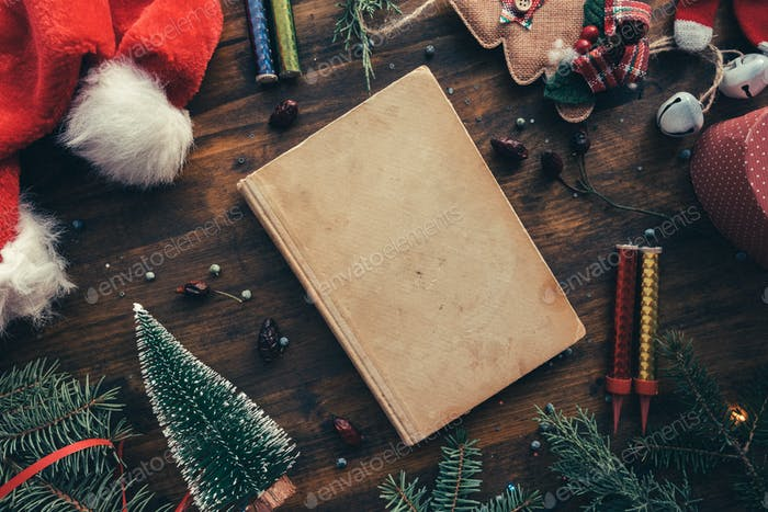Vintage book among Christmas decoration, flat lay top view