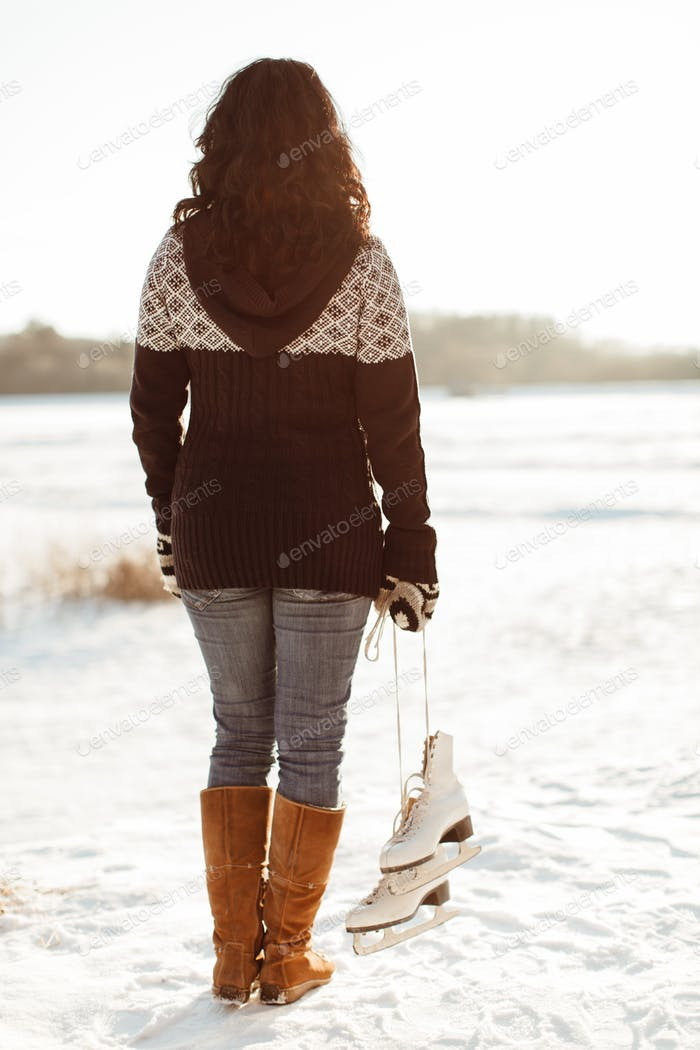 Rear view of a woman carrying a pair of skates tied together