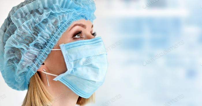 Close up portrait of female medical doctor or nurse wearing protective cap and mask