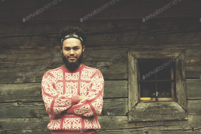 portrait of young hipster in front of wooden house
