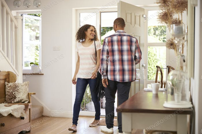 Man Opens Front Door For Woman Returning Home From Work