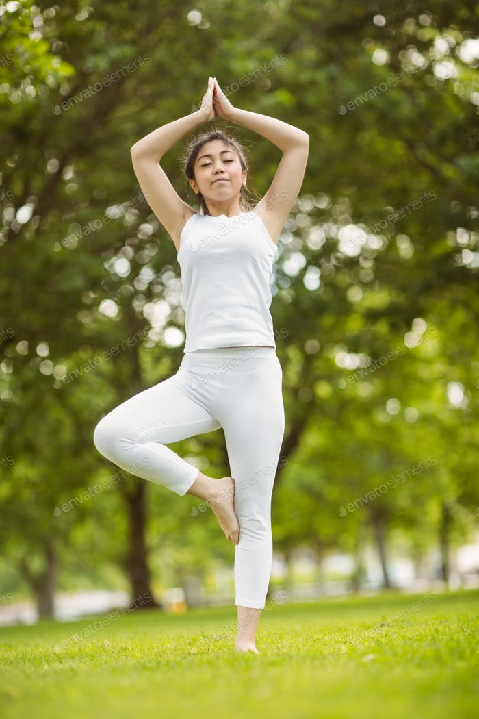 Full length of fit young woman standing in tree pose in the park