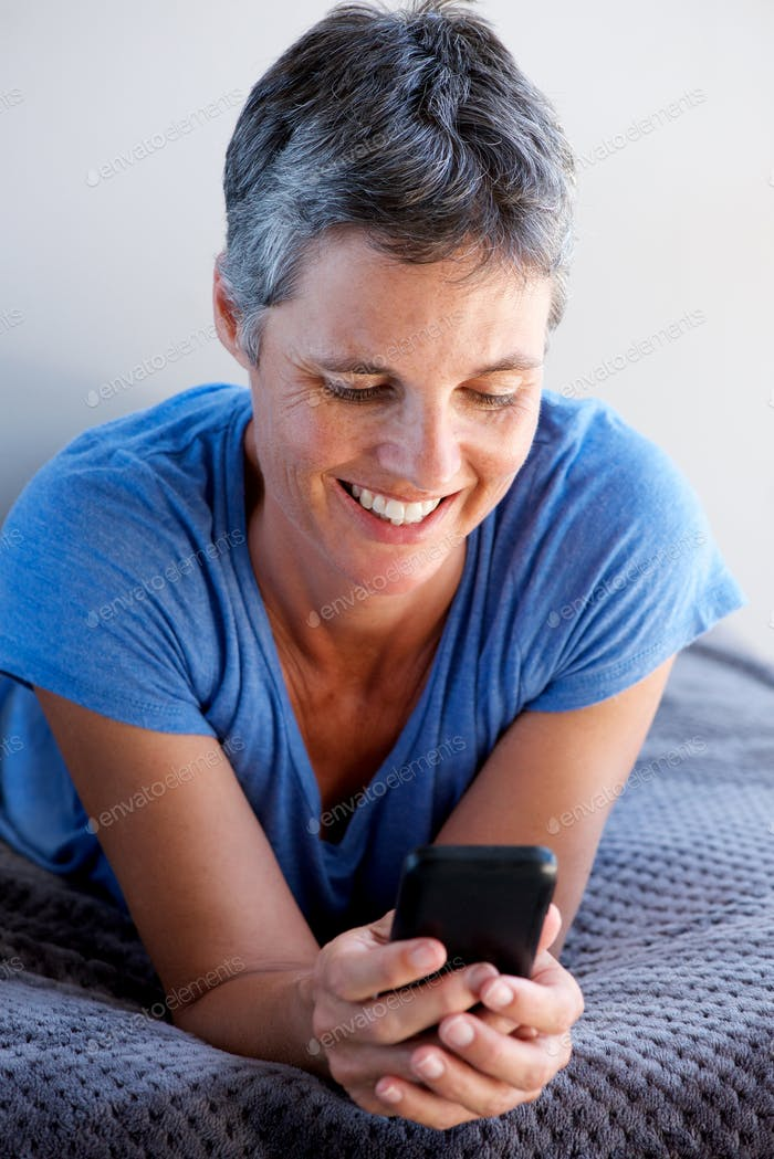 Close up attractive mature woman smiling and using mobile phone