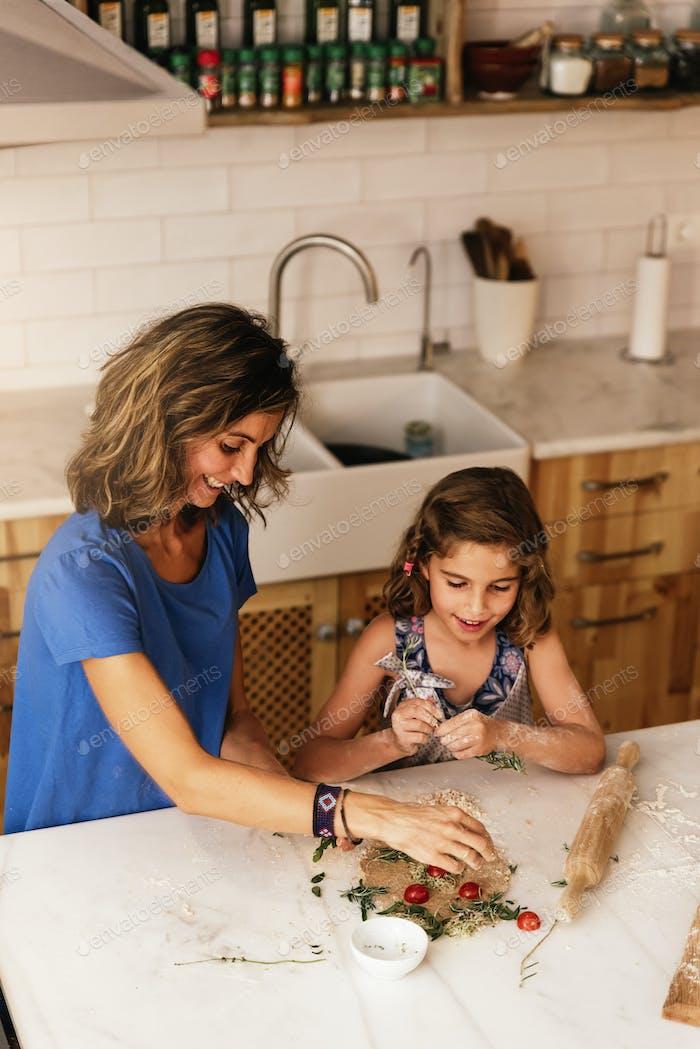 Kleines Mädchen, das mit ihrer Mutter in der Küche kocht.