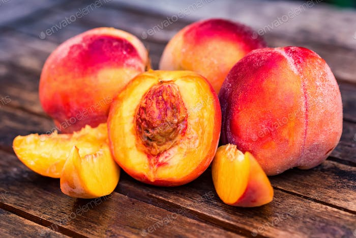 Fresh ripe peaches and slices on wooden table