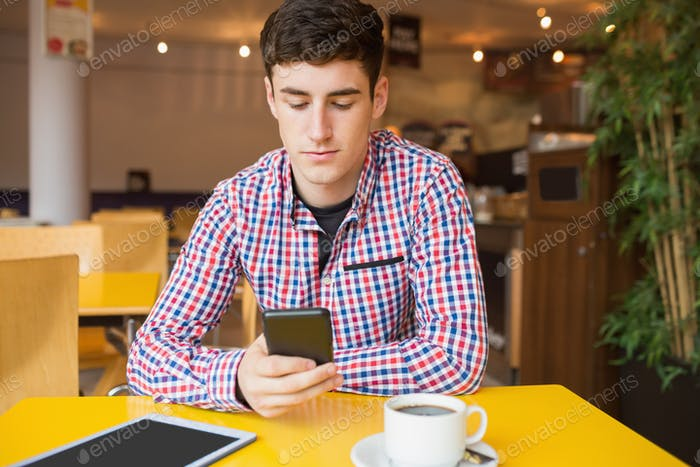 Young man using mobile phone at table in cafe