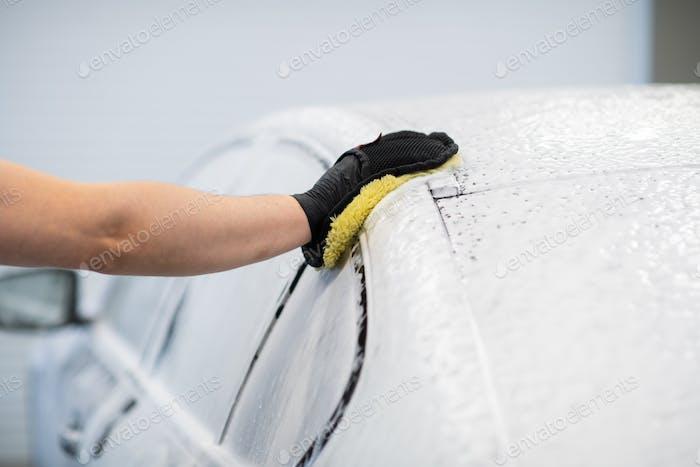 Mann waschen ein seifenartiges schwarzes Auto in einem Reinigungs- und Detaillierungsservice
