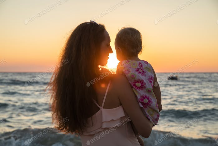 Mother and baby having fun at sunset beach