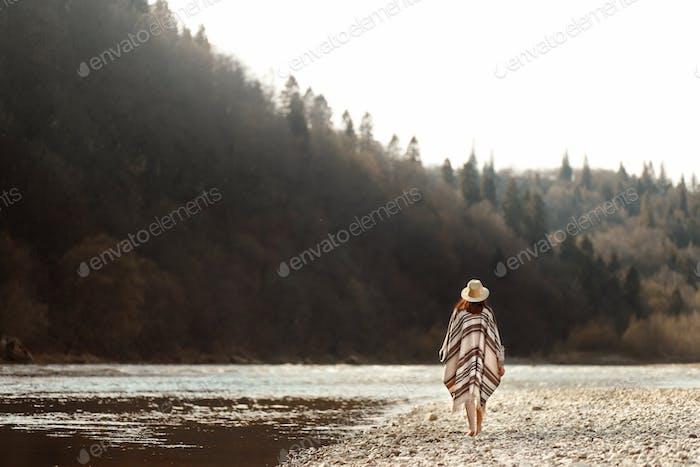 hermosa mujer hipster caminando en la playa del río en las montañas