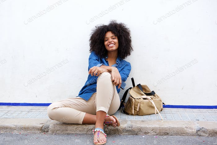 Happy woman sitting with mobile phone and bag