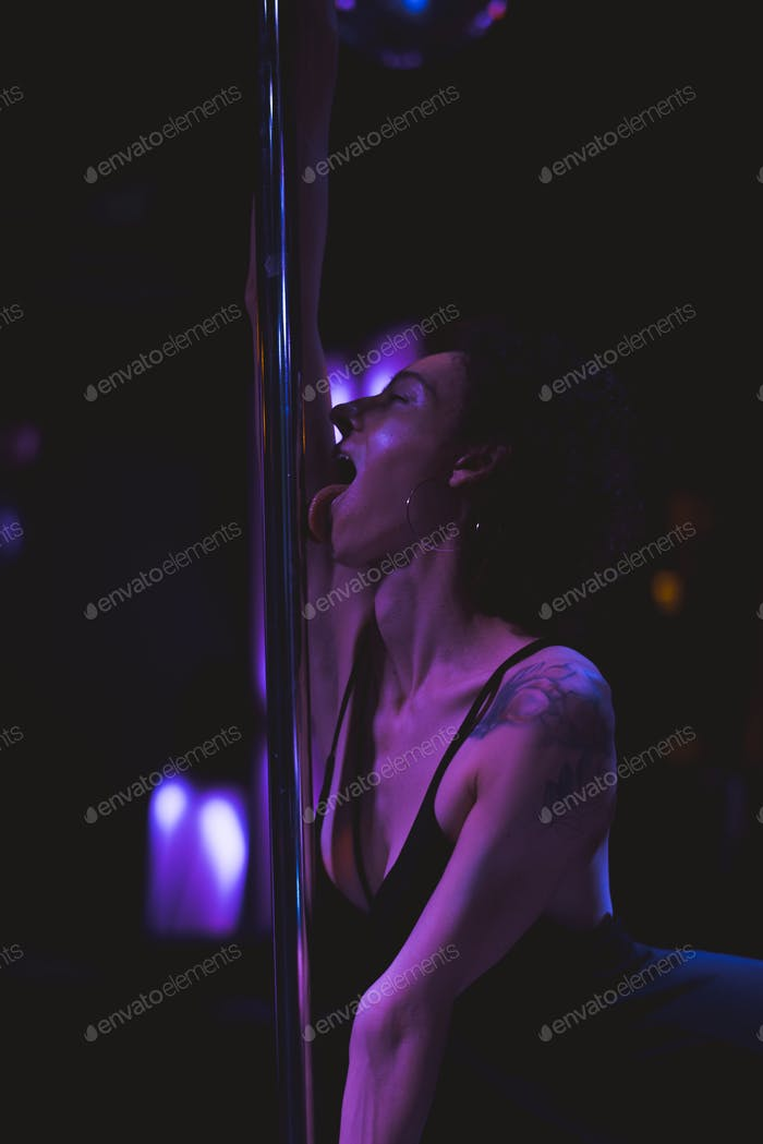 Woman having fun with a stripper pole