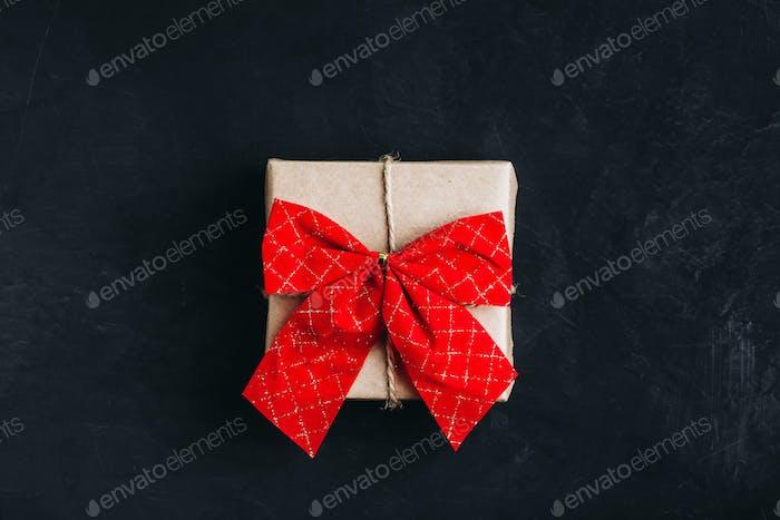 Weihnachtsgeschenk Box Weihnachtsgeschenkbox mit roter Schleife auf dunklem Steinhintergrund.