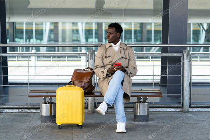 Black traveler man with suitcase sitting on bench in airport terminal, calling and looking for taxi