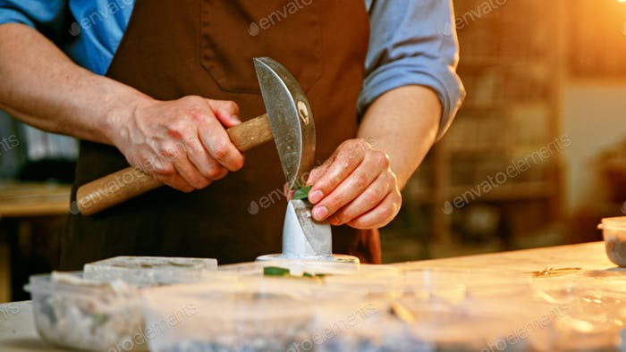 Working man with a hammer in workshop