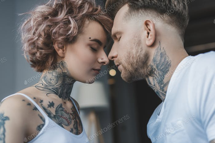 Young Tender Tattooed Couple touching Noses With Closed Eyes