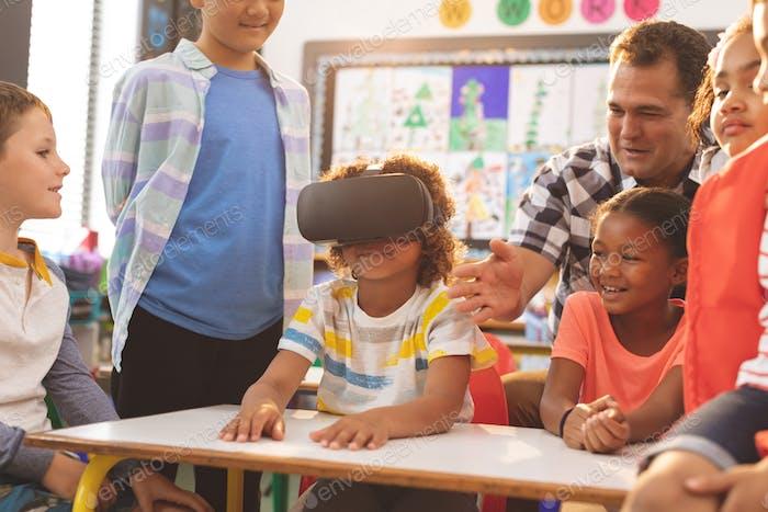 Vorderansicht eines Schülers mit Virtual Reality Headset mit seinem Klassenkameraden und Lehrer in der Schule