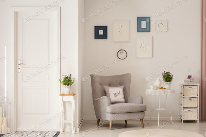 Flowers on table next to grey armchair in white living room inte