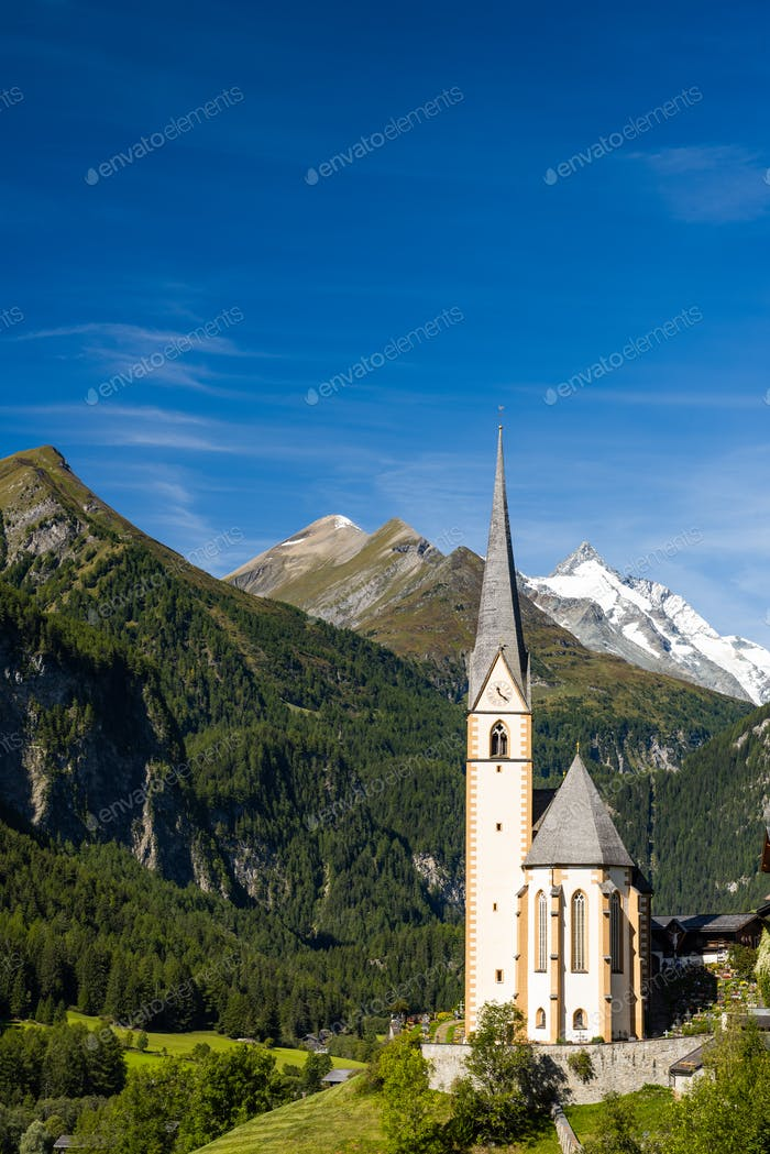 Pitcuresqe Church in Austria Village. High Alps Mountains in Bac