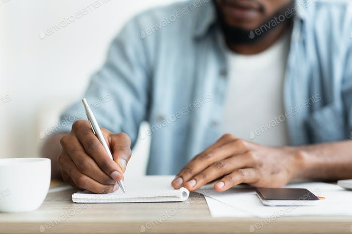 African american businessman writing down his plans to notepad