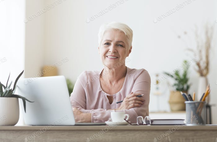 Attractive old lady posing at workdesk at home