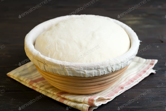 Freshly cooked yeast dough in a basket for baking of fresh natural cakes and cookies on a dark