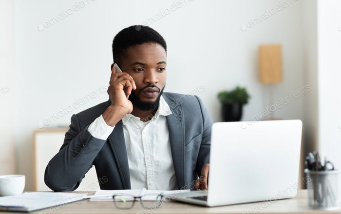 Focused afro businessman talking on cellphone and working on laptop