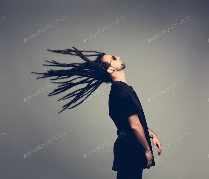 Young man flipping his dreadlocks back.