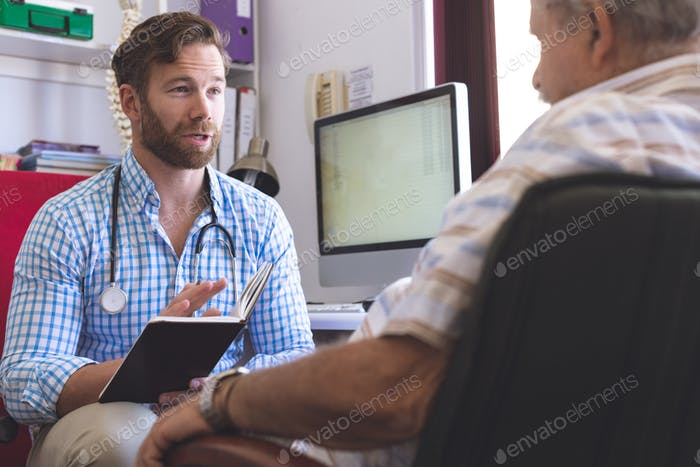 Male doctor prescribing medicament to senior man in clinic room