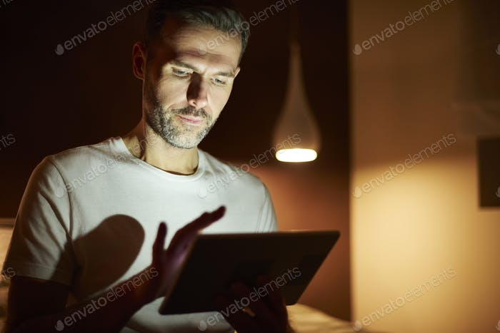 Focused man using tablet at night