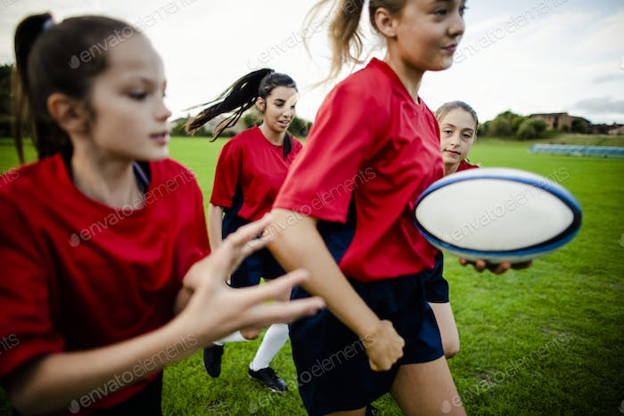 Female rugby players playing on the field