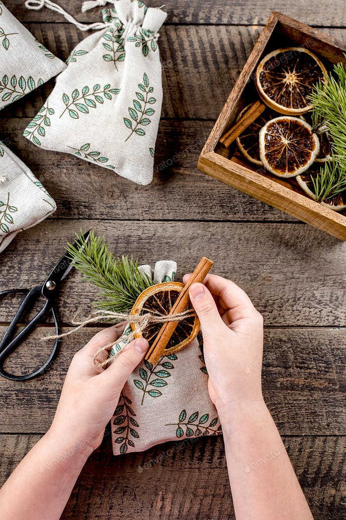 Christmas zero waste packaging. Girl decorating textile gift pouches by dry orange and cinnamon.