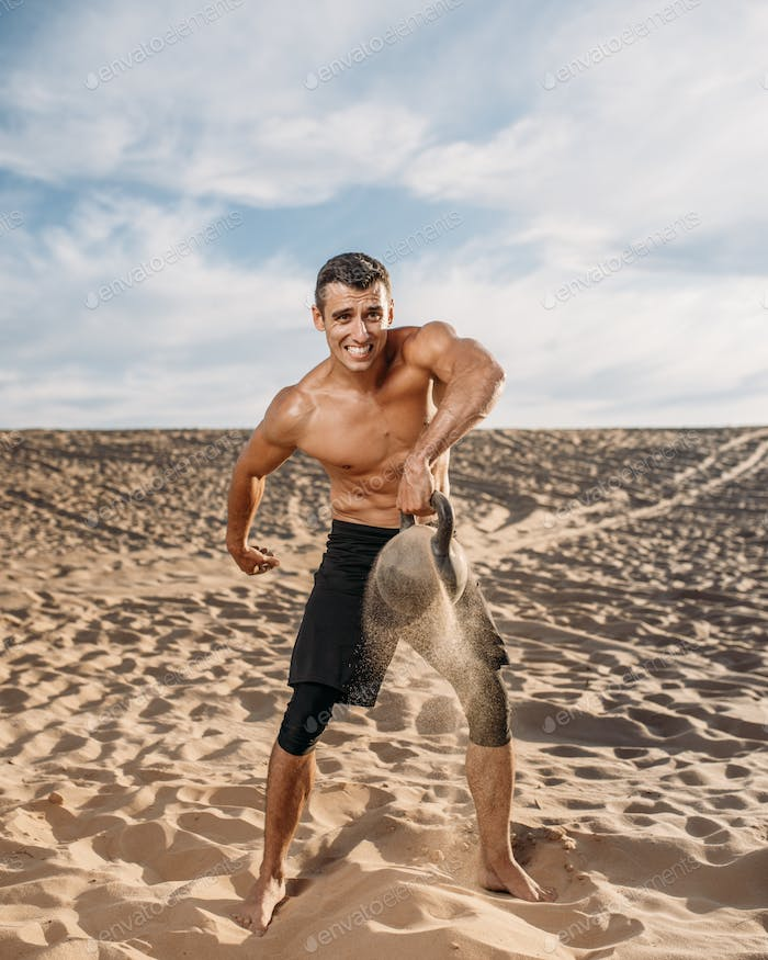 Athlete with kettlebell in desert, flying sand