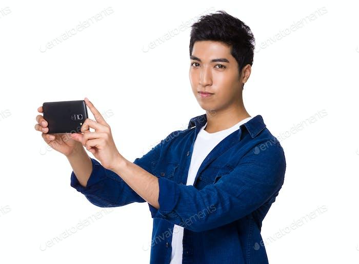 El hombre usa el teléfono móvil para tomar fotos