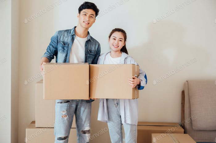 Young couple moving boxes in new home