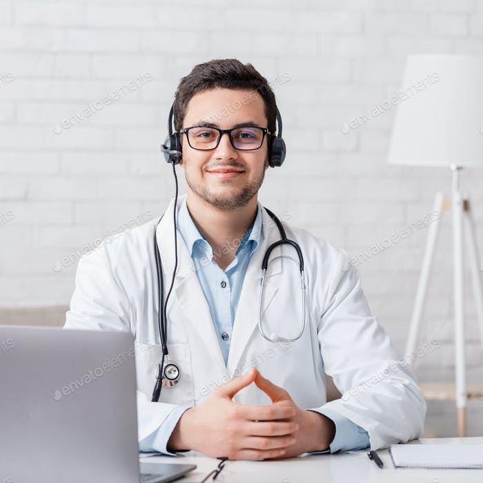 Work at home online. Doctor sits at table with laptop in interior