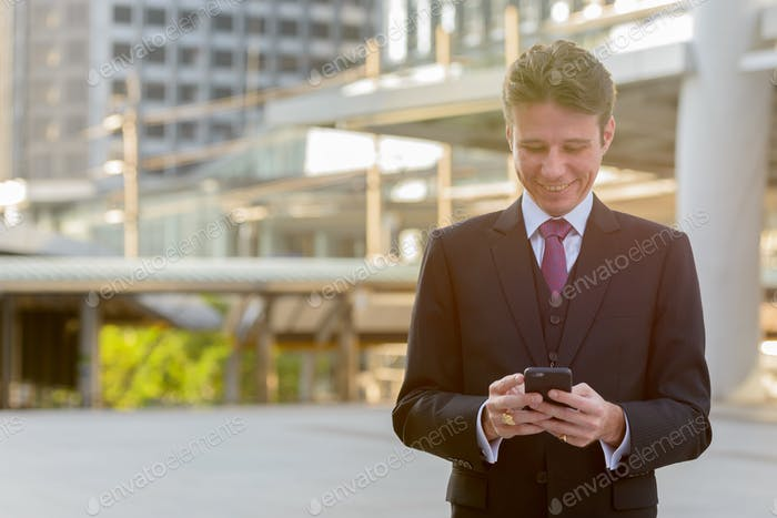 Happy businessman smiling and using mobile phone in front of mod
