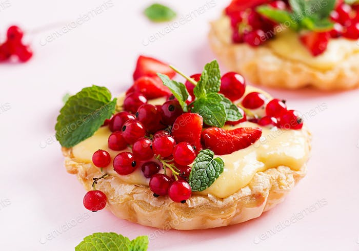 Tarts with strawberries, currant and whipped cream decorated with mint leaves.
