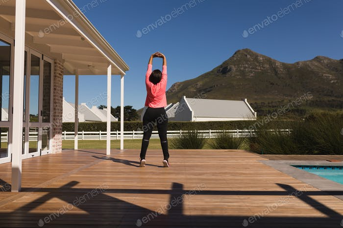 Middle-aged woman performing stretching exercise in the backyard of home