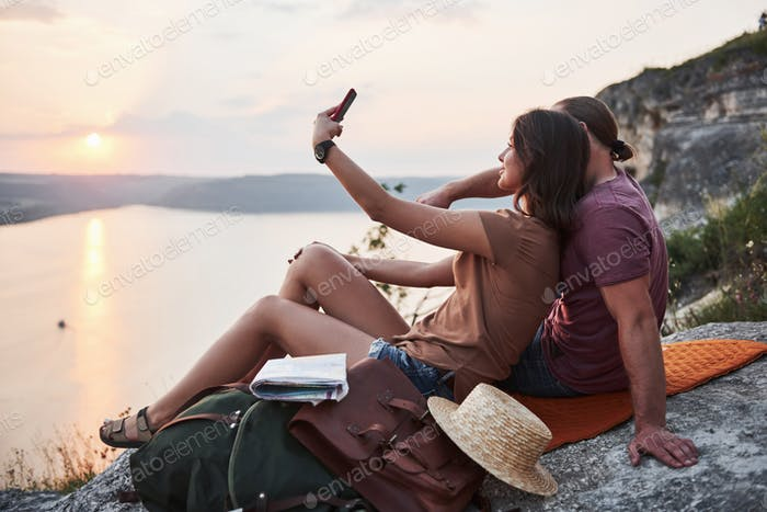 Hugging couple with backpack sitting on top of rock mountain enjoying view coast a river or lake
